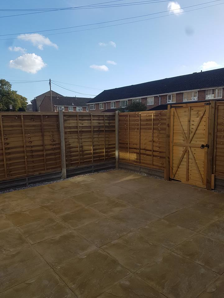 Green Overlap Fencing Panels with Concrete Gravel Boards